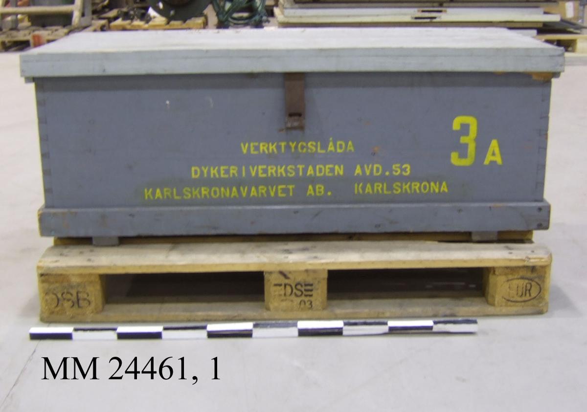 """Gråmålad låda av trä med ljusgrått lock. Locket är försett med bygel för hänglås. På lådans framsida finns texten """"VERKTYGSLÅDA 3A, DYKERIVERKSTADEN AVD. 53, KARLSKRONAVARVET AB. KARLSKRONA"""" i gult. På lådans kortsidor finns svarta handtag av metall. Lockets insida har en innehållsförteckning över de verktyg som ska finnas i lådan. Lådan har avbildade verktyg med svart färg och verktygshållare av läder."""