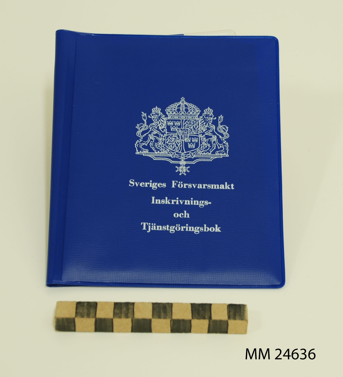 """Inskrivnings- och tjänstgöringsbok. Fodral av blå plast med vit tryckt text: """"Sveriges Försvarsmakt Inskrivnings- och Tjänstgöringsbok"""" samt stora riksvapnet.  På baksidan tryckt text i vitt: """"M7102-383430-9. Utgåva 3. (VPV). 75-05. 50 000 ex. LF-ALLF 405 75 231"""". Plastfickor på fodralets insida. På ena sidan finns terminslönekort. På andra sidan finns tjänstgöringskort, krigsplaceringsorder, en folder kallad """"Minneslista"""" samt en identitetsbricka av plåt. Foldern """"Minneslista"""" innehåller ett sammandrag av de viktigaste bestämmelserna som värnpliktiga behöver känna till. Foldern giltig efter 1971."""