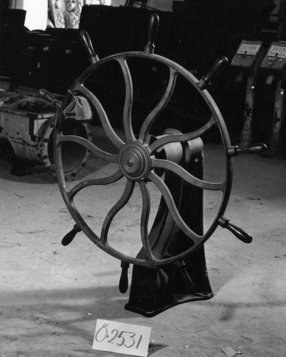 Ratt från ASLÖG. 10 spakar på ratten. Axel med lagerbock, försedd med vals och två trissor för drilltåget. Tillhörande kilar, 2 st, samt 5 st skruvbultar av järn för lagerbockens fästande till däck.