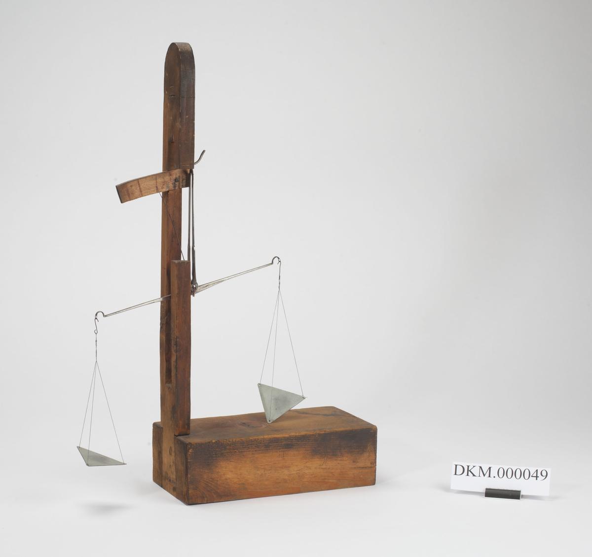 På en rektangulær trekasse er det festet en stang, og på den er vekten hengt. Vekten har to sett skåler som er flate og trekantformede. Skalaen er tegnet for hånd på ett trestykke som er innfelt i stanga.