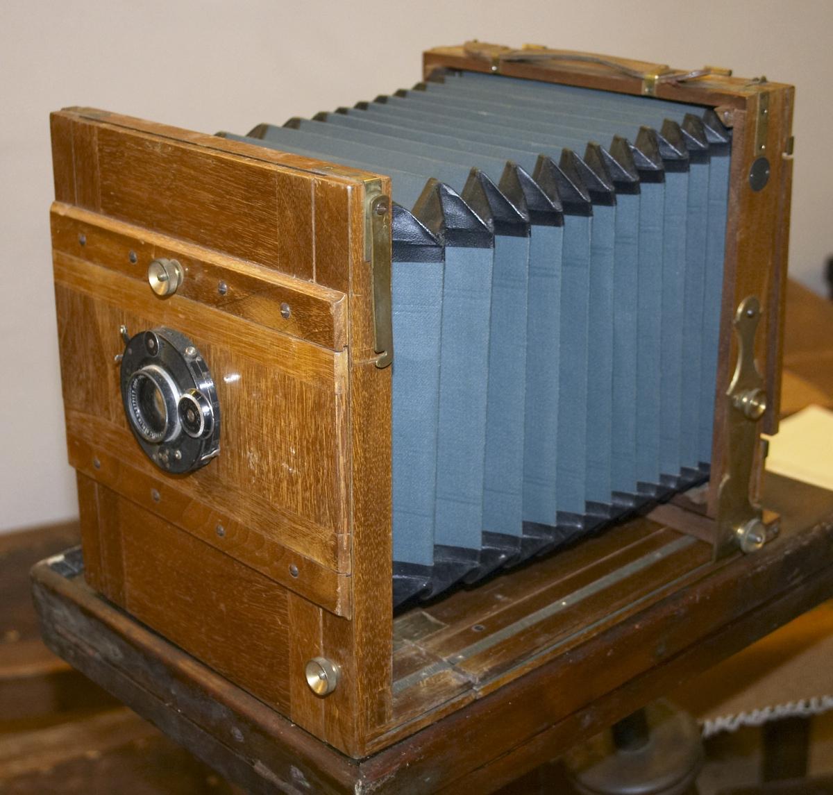 """Gammelt fotoapparat med belg. For glassplater. Medfølgende veske med 3 oppbevaringsesker for totalt 6 eksponerte glassplater. Boks med 14 bilder på glassplate 17,8 x 12,9 cm. En ukjent lukkermekanisme (passer ikke til kameraet da dette har såkalt """"Compur"""" objektiv med innebygget lukker). Mekanismen kan ha tilhørt et tidligere kamera. En tom film-boks. Man kan finne ut mer om slike kamera i boken """"kameraboken"""" skrevet av Brian Coe."""