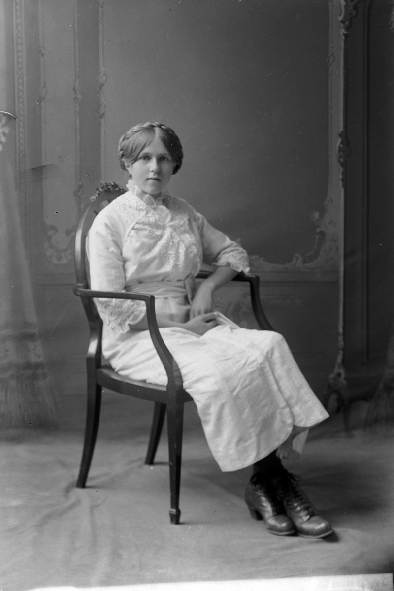 Studioportrett av kvinne i stol.