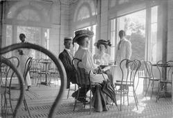To kvinner og en mann sitter i restauranten i badehuset i Pr