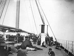 """Passasjerer som slapper av på dekket til skipet """"Laxavia""""."""