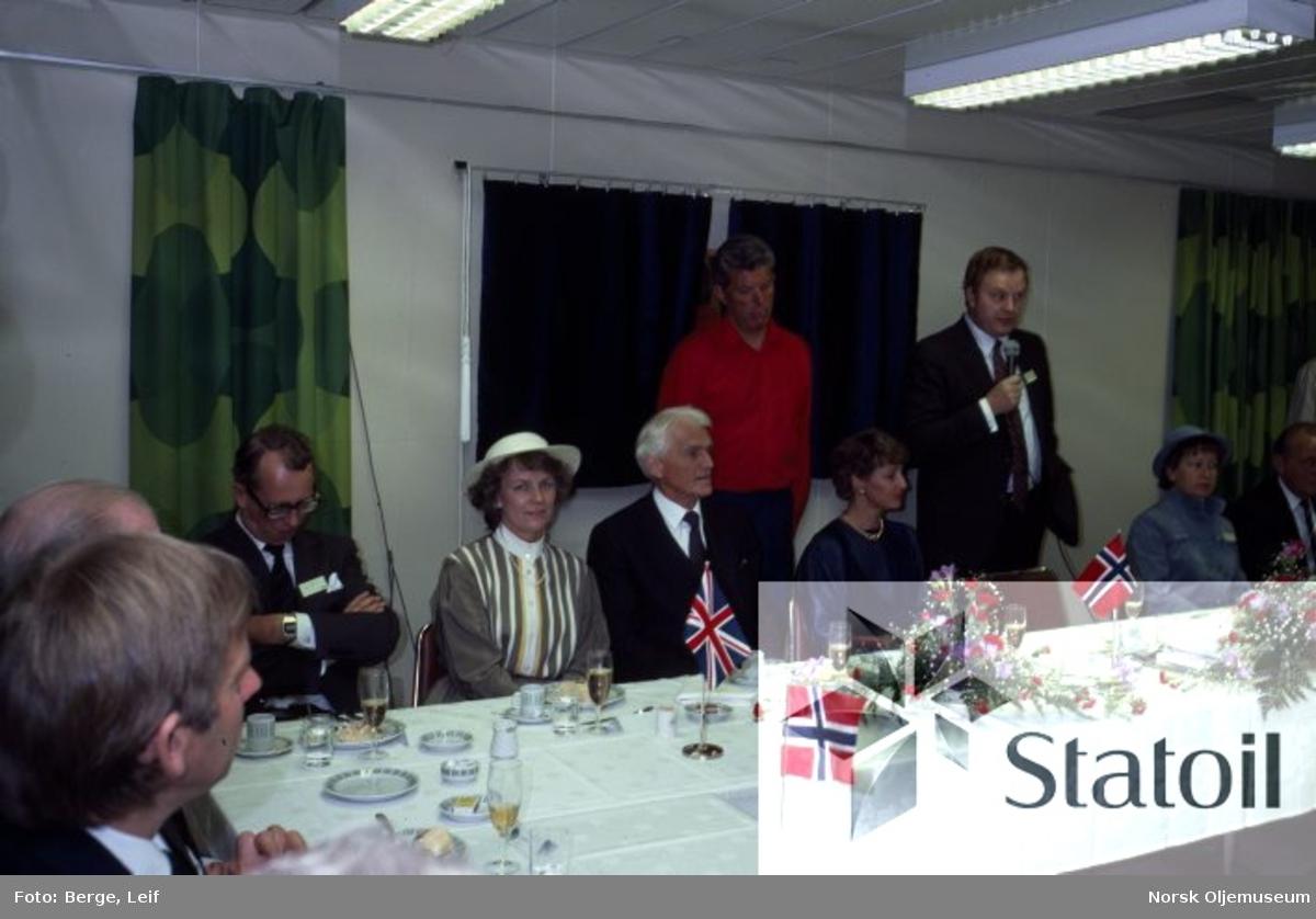 Dåpsdag for Statfjord C.  Mike Smith fra Mobil holder tale, og ved middagsbordet t.v. for ham sitter gudmor HKH Kronprinsesse Sonja, Kåre Kristiansen, Jan P. Syse samt flere ukjente gjester.  Agnes og Arne Rettedal skimtes helt ute i høyre bildekant.