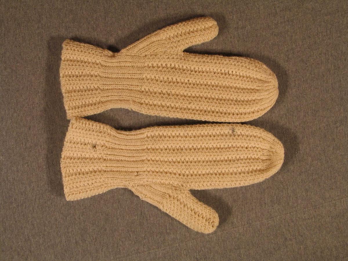 Form: Mønsterstrikka vottar i ein farge. Mønsteret utgjer striper på vottane.  Strikka t tunt garn på tunne pinnar. Mønsteret er kjent frå andre vottar på SuM. Tomlane er strikka for seg sjølve og sydde på vottane.