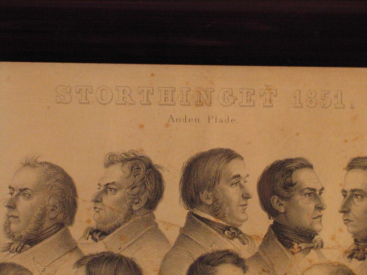"""Litografien syner portrett av 51 stortingsmedlemmer, dei fleste i profil. Alle er refererte med nummer til eit namneoppsett under. På venstre sida av namna er trykt """"J N Prahm del"""", på høgre sida """"EM BærenstZen & Co lith Inst Kjøbnh""""  Liggande format, sett inn i brei råme med konveks profil. På framsida og kantane er råma overflatebehandla med beis og lakk."""