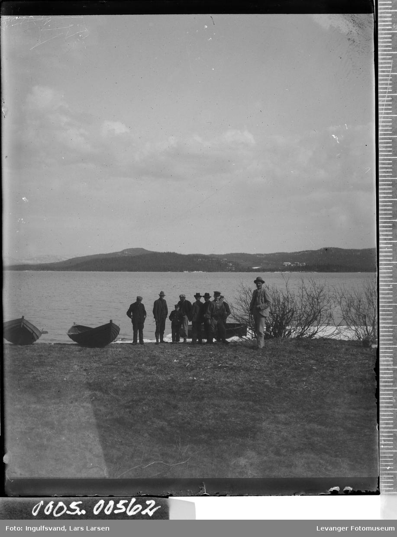En gruppe mennesker og båter ved vann.
