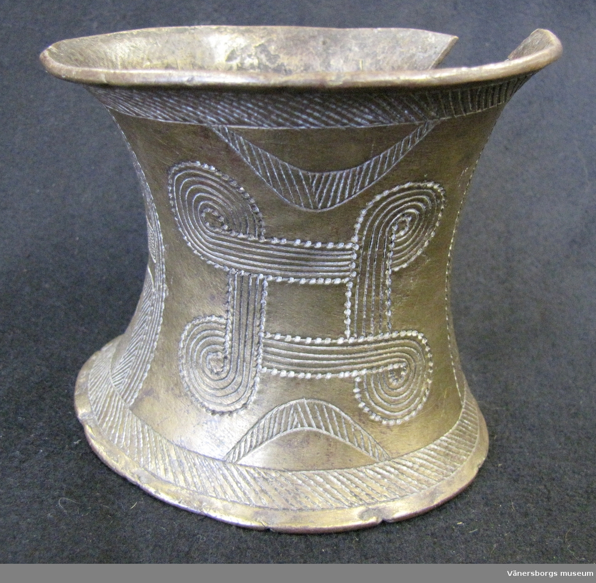 Armband, cylindriskt konkav i formen. Ena sidan av armbandet är öpen. Armbandet är rikt dekorerad med graverade mönster.