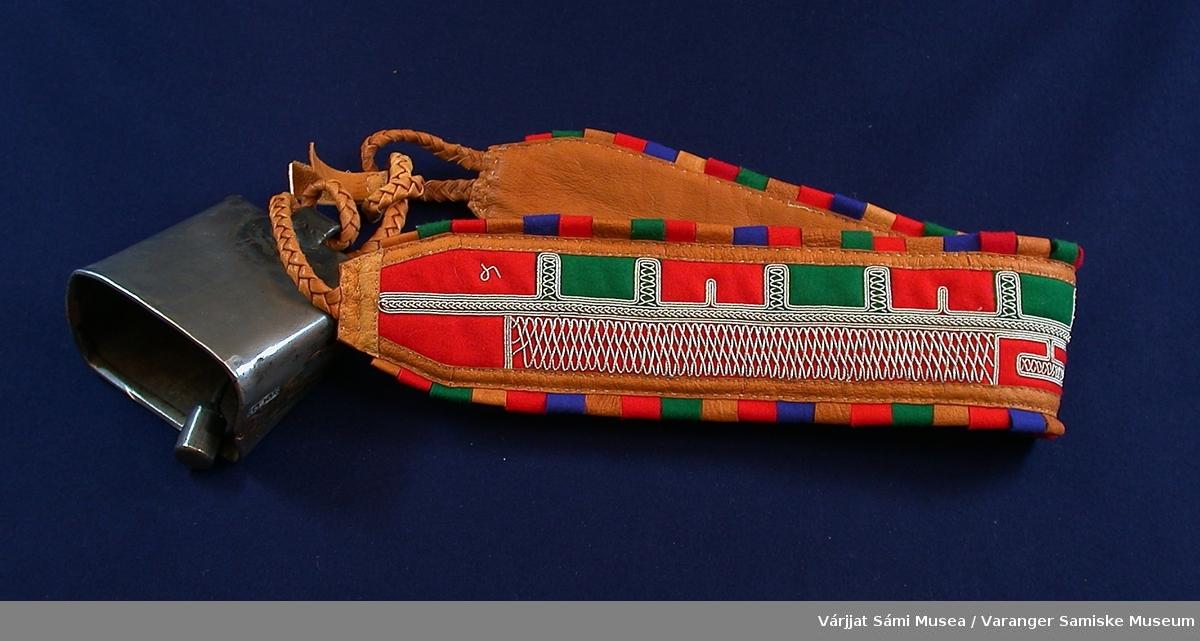 Bjelleklave av skinn og klede brodert med tinntråd. Klaven er hovedsakelig av skinn, dekorert med klede i geometrisk mønster. Tinntråden er en del av dette mønsteret og er nærmest brukt til å skille de ulike kledebitene/fargene. Tinntråden er sydd på i løkker og buer, som åpne 8-tall. Bjella er festet til klaven med tvunnede skinnsnorer.