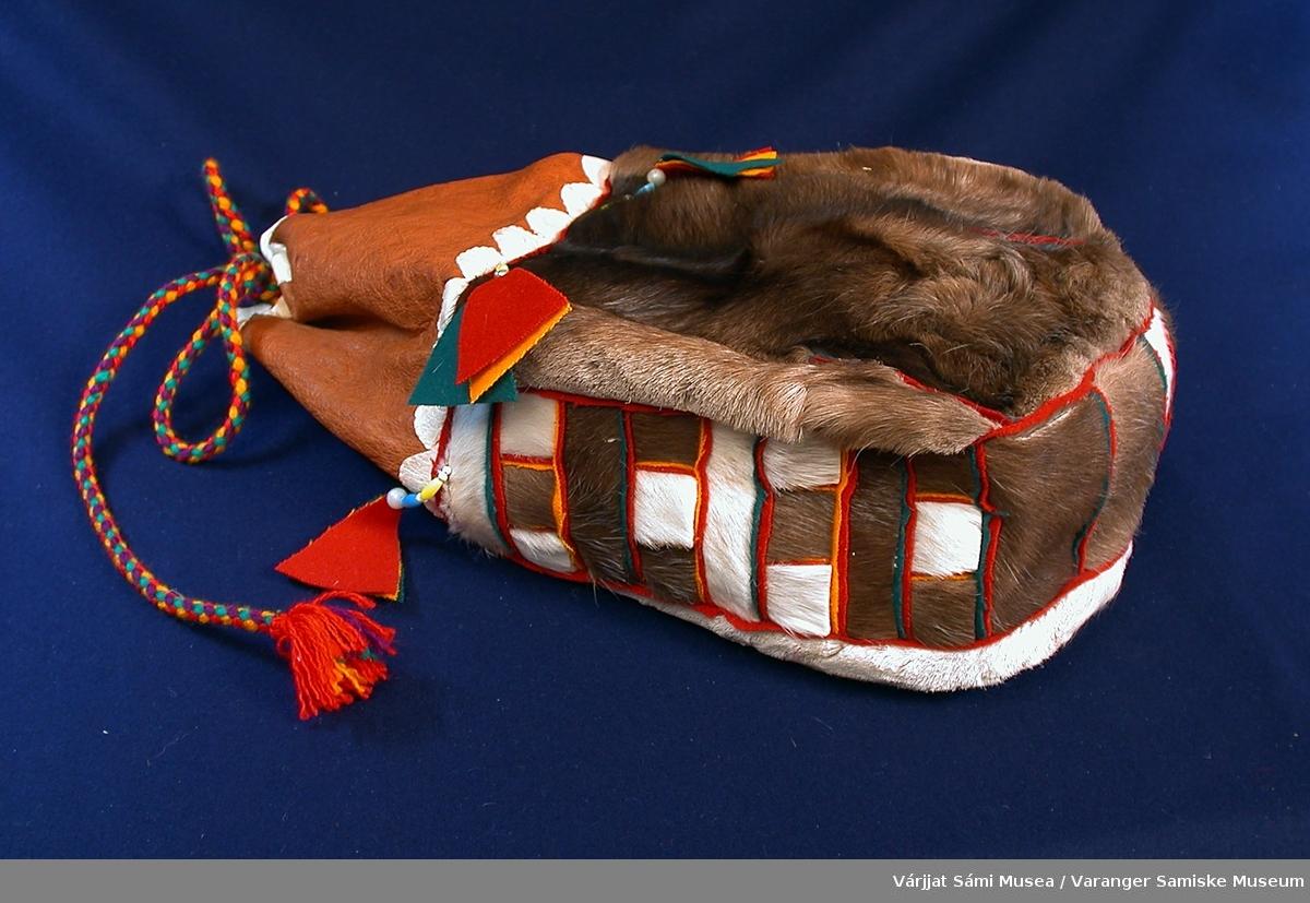 Sekk av reinskinn (med hår) og klede. Den har form som en stor kaffepose, med åpning og surring oppe. 3/4 av front og bakstykke er av reinskinn. Den øverste (mot åpningen) 1/4 og bunn og sider er av klede i ulike brunfarger, hvitt og rødt. Sekken er pyntet med trekantdusker av klede i rødt, blått og gult i overgangen meloom skinn og klede. duskene henger fast i en kort perletredd snor. Perlene er gule, lyseblå og hvite. Sekken trekkes igjen med tvunnede ullsnorer i gult, rødt og blått.