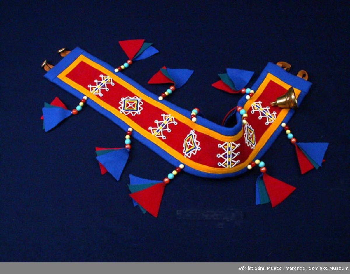 Bjelleklave for rein. Bunnfargen rødt klede, pyntet med gult og blått klede. Klaven er også pyntet med perler. 1 stk divga, liten bjelle.