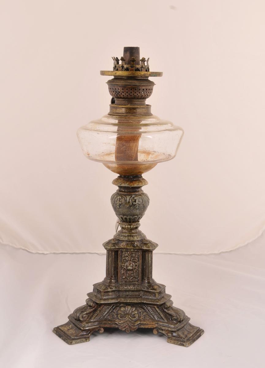 Parafinlampe med trekanta malmfot, glaskolbe og veke. Med lampeglas, knust i toppen. Utan kuppel.