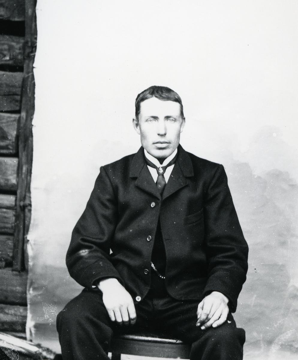 Dresskledd mann, sittende foran lerret på tømmervegg