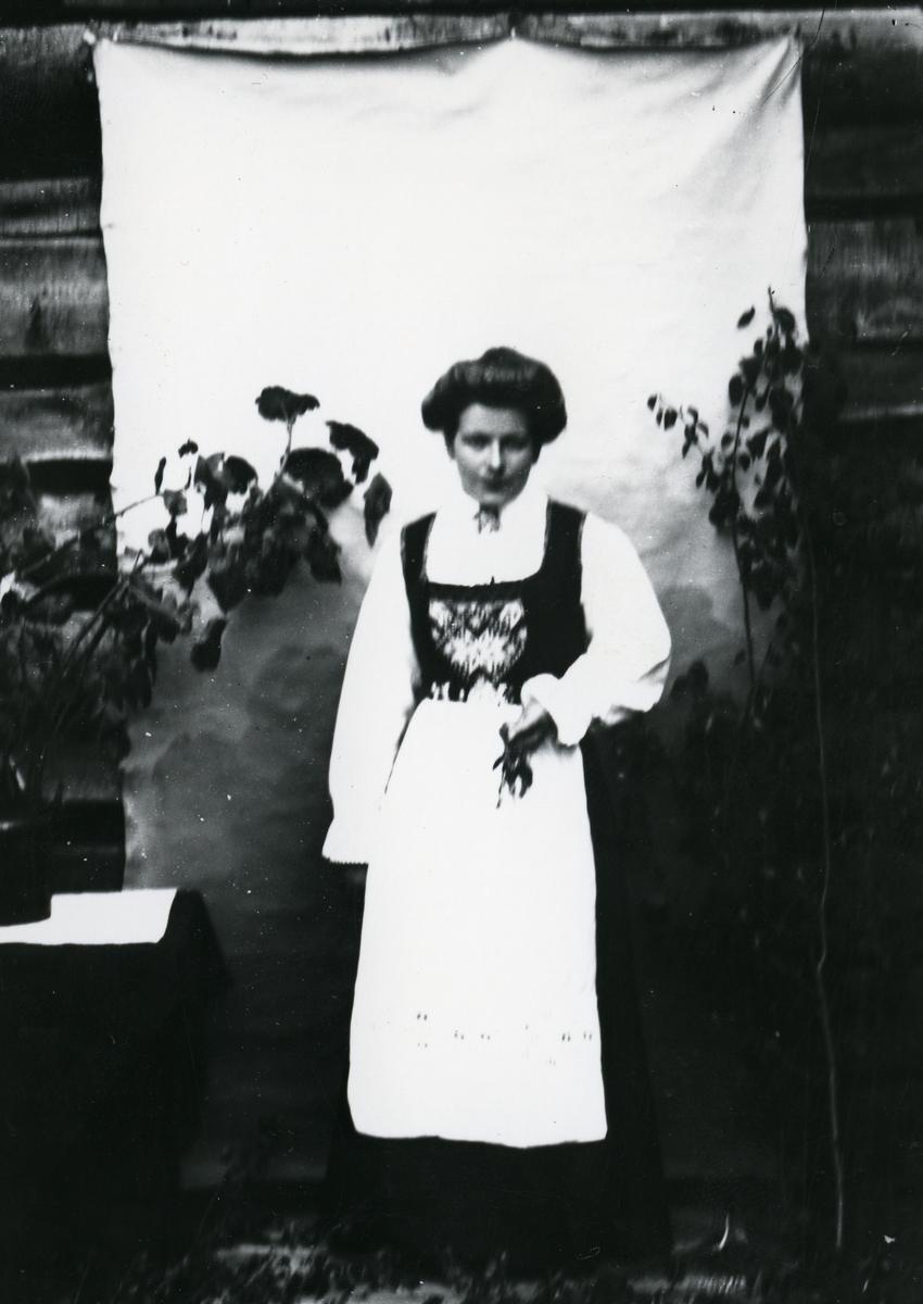 Kvinne kledd i nasjonaldrakt, avbildet i helfigur foran lerret på husvegg