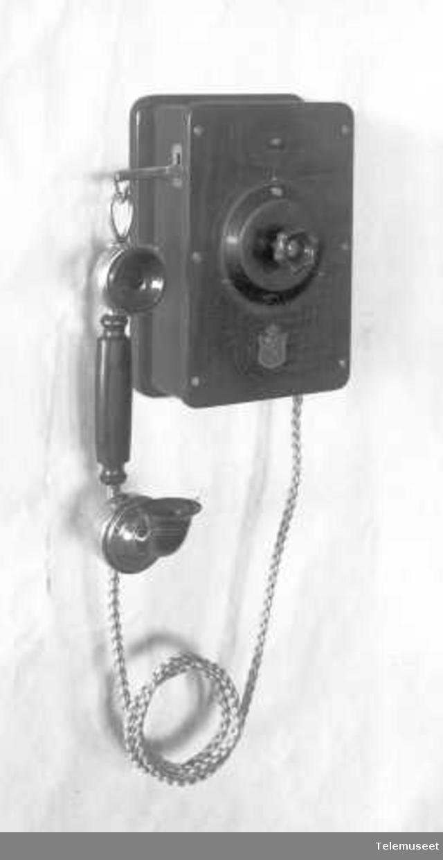 Telefonapparat, lokalt veggapparat i tre, mtlf.hengende, for 10-30 e.lj. KLokke likestrøm. Elektrisk Bureau.