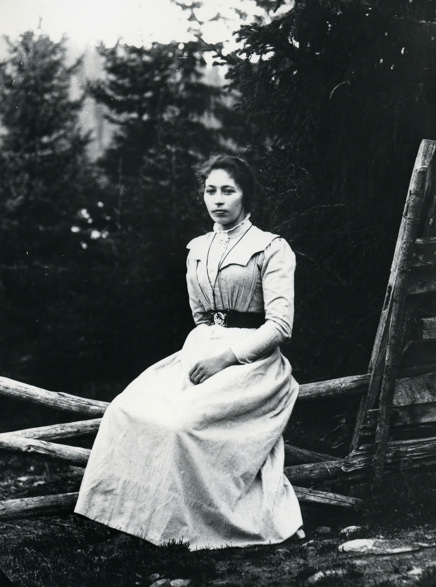 Kvinne i lys kjole, sittende på gjerde, med skog i bakgrunnen