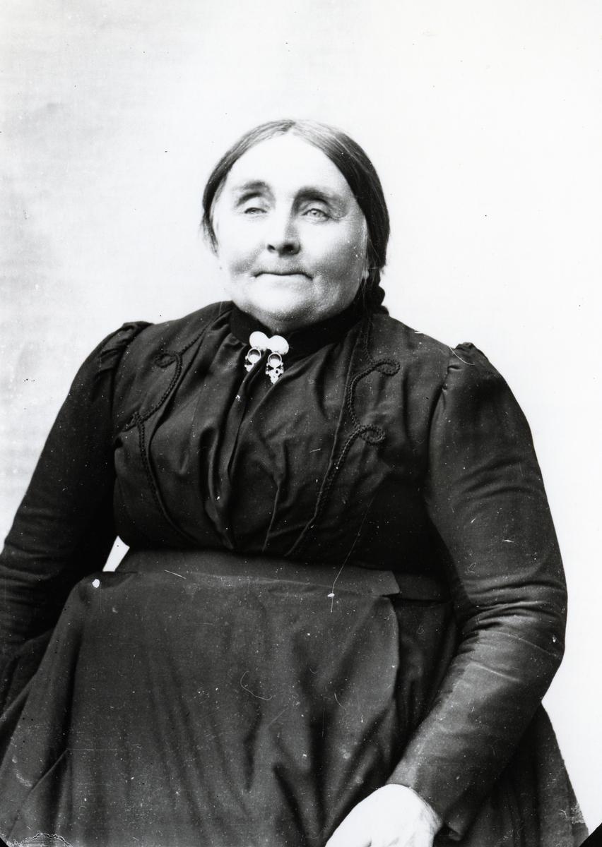 Eldre kvinne i halvfigur, lerretbakgrunn