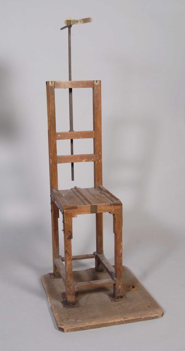 På stolryggen er det festet et regulerbart metallstativ med høydemåler, støtte og passer for avlesing av personens fysiske mål: hode, hals, ryggens høyde etc. På stolryggens høyre side finnes en målestokk i centimeter fra 74 til 94.