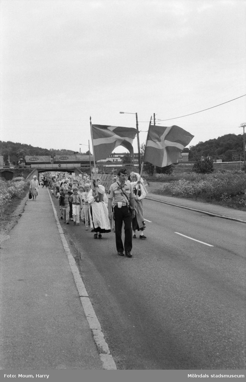 """Nationaldagsfirande i Kållered, år 1984. """"Hallenskolans barn och lekskolebarn på väg till Ekenskolan.""""  För mer information om bilden se under tilläggsinformation."""