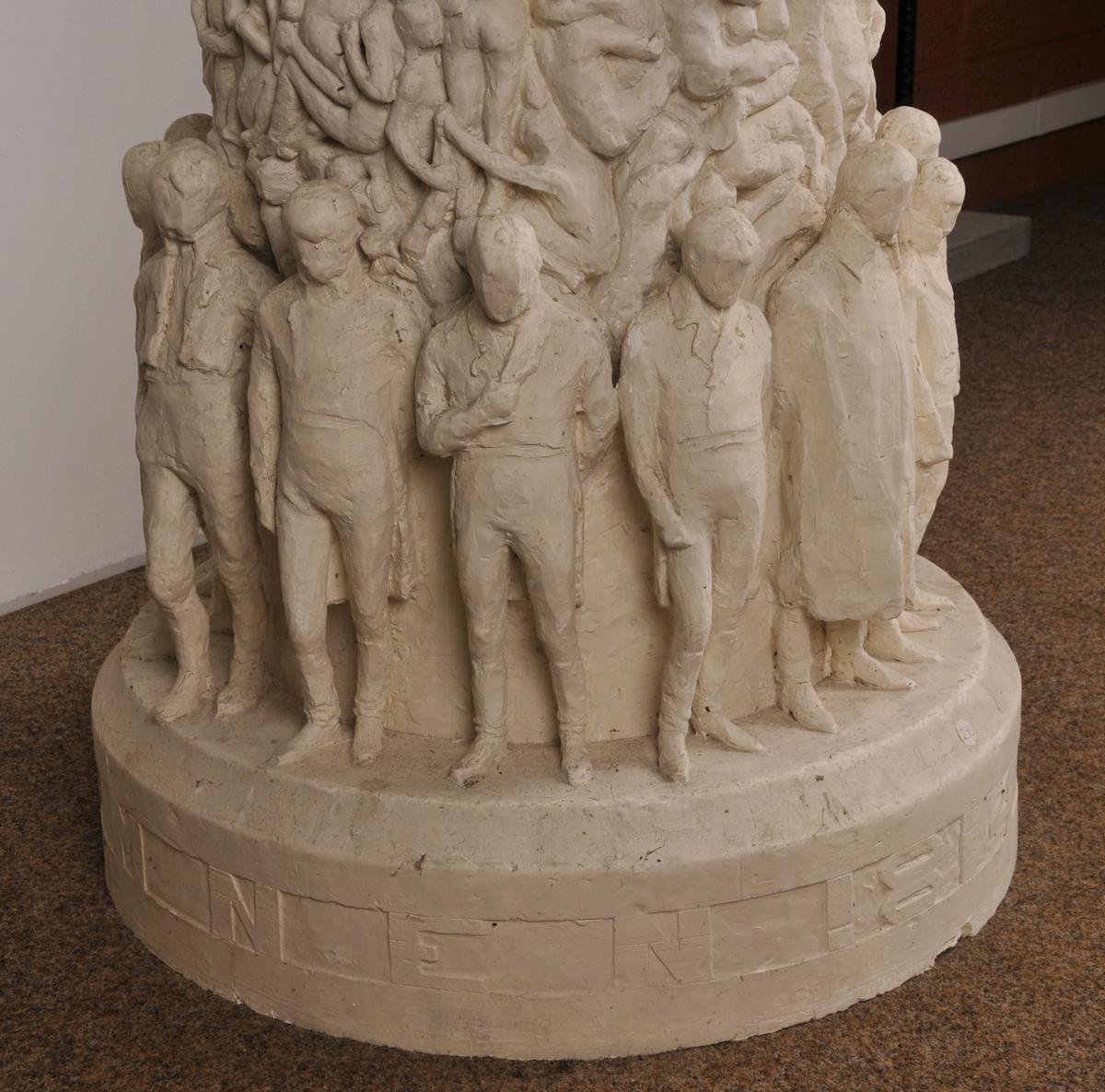 Søyle dekt av relieff av nakne menneske. Rundt foten av søyla står ein ring av symbolske fridomsfigurar (Eidsvoldsmennene?). På toppen av søyla sit den ekstatiske Fossegrimen som lokkar mennesket med spelet sitt.