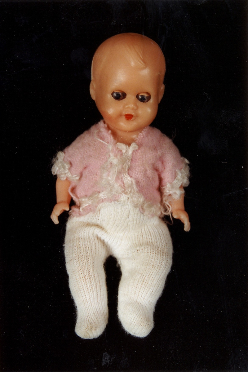 Sovedukke med bevegelige armer og bein. Rosa bukse, hvit jakke.