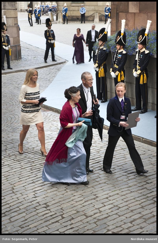 Kronprinsessbröllopet. Dokumentation av bröllopet mellan Kronprinsessan Victoria och herr Daniel Westling 19 juni 2010. Gästerna anländer till Storkyrkan. Kvinna i flerfärgad, randig överdel och ljusblå kjol, vinröd sjal över axlarna, mintgrön sjal i handen och mörk, turkos kuvertväska, man i frack. Journalisten Ebba von Sydow i naturvit klänning med svarta ränder och strass, samt beiga pumps.