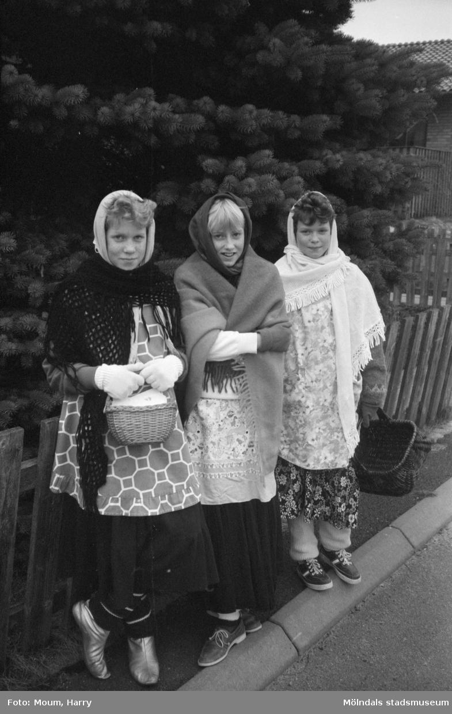 """Tre flickor utklädda till påskkärringar i Livered, Kållered, år 1983. """"Vår fotograf hade svårt att finna några påskkärringar, men lyckades till slut knäppa Charlotte och Marie Olsson med deras väninna Anneli Andersson i Livered.""""  För mer information om bilden se under tilläggsinformation."""