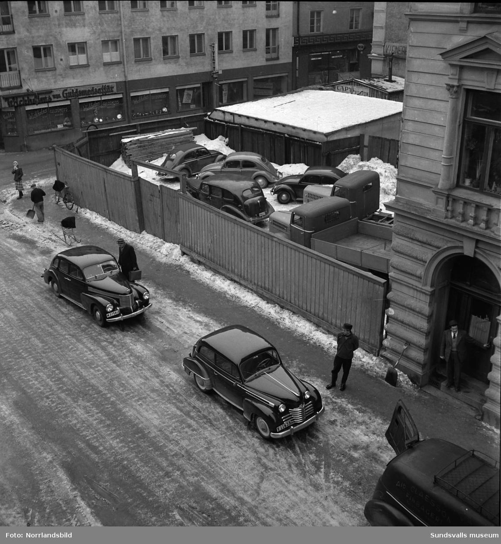 Översiktsbild vid Trädgårdsgatan-Nybrogatan med parkerade bilar på en innergård och Wickholms guldsmedsaffär.