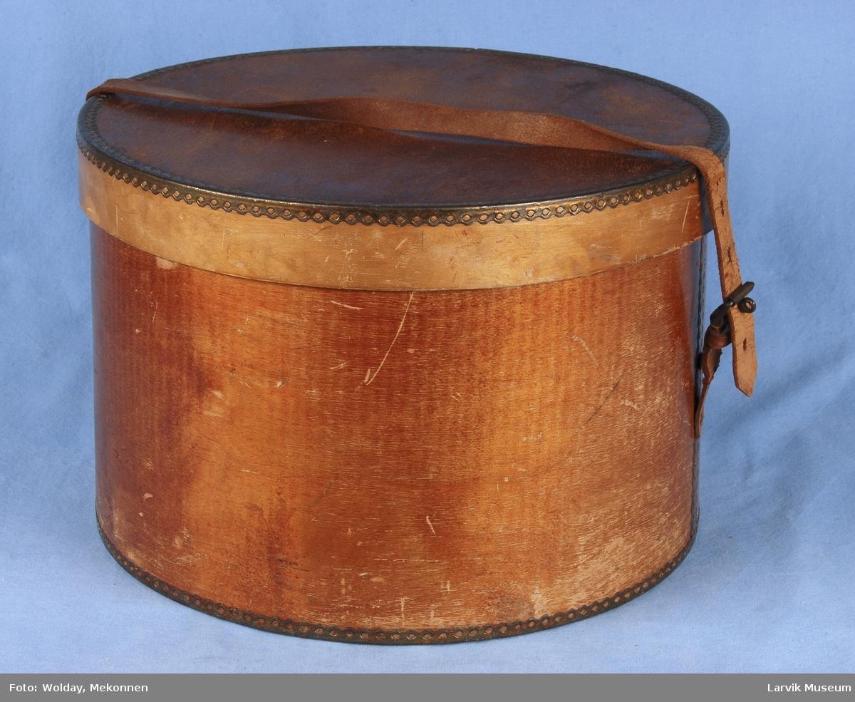 Form: Sylinder form. Lokk. Delene er festet med metallbånd med hullmønster. To reimer er festet til hver sin side, for festing over lokket, den ene med spenne. Festes i siden. Man kan bære i denne.