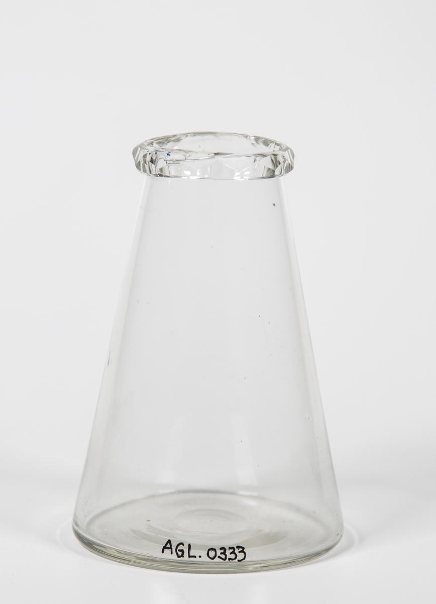 Vasen smalner av mot åpningen og avsluttes med slipt pyntekant.
