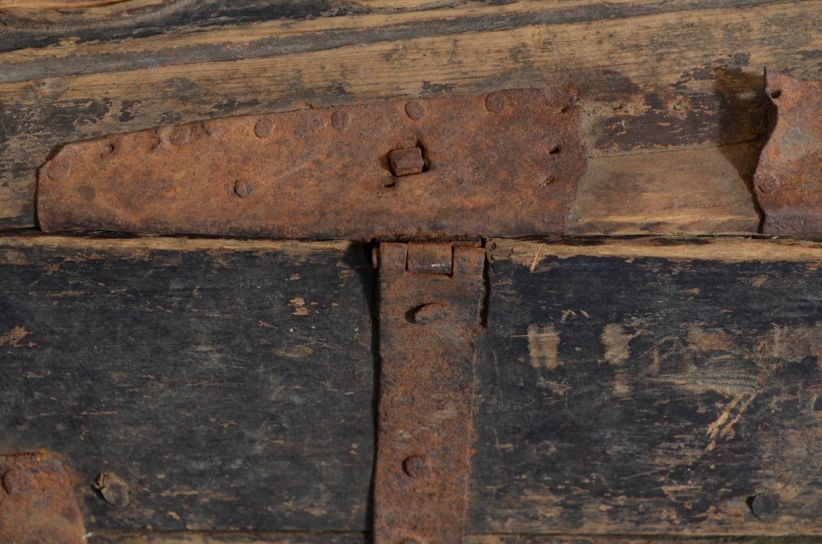 """Feleskrin av Bjørk. Skrinet er satt sammen med trenagler og forsterket med jernbeslag. Merker etter lås. Skrinet er malt med mørkebrun maling. Påskrift på siden med lysegrønt: """"Knud (?) Larsen...1825""""  Lokket er jernhengslet. Buet med utskåret rokokkoskurd. Lokket er i svært dårlig forfatning."""