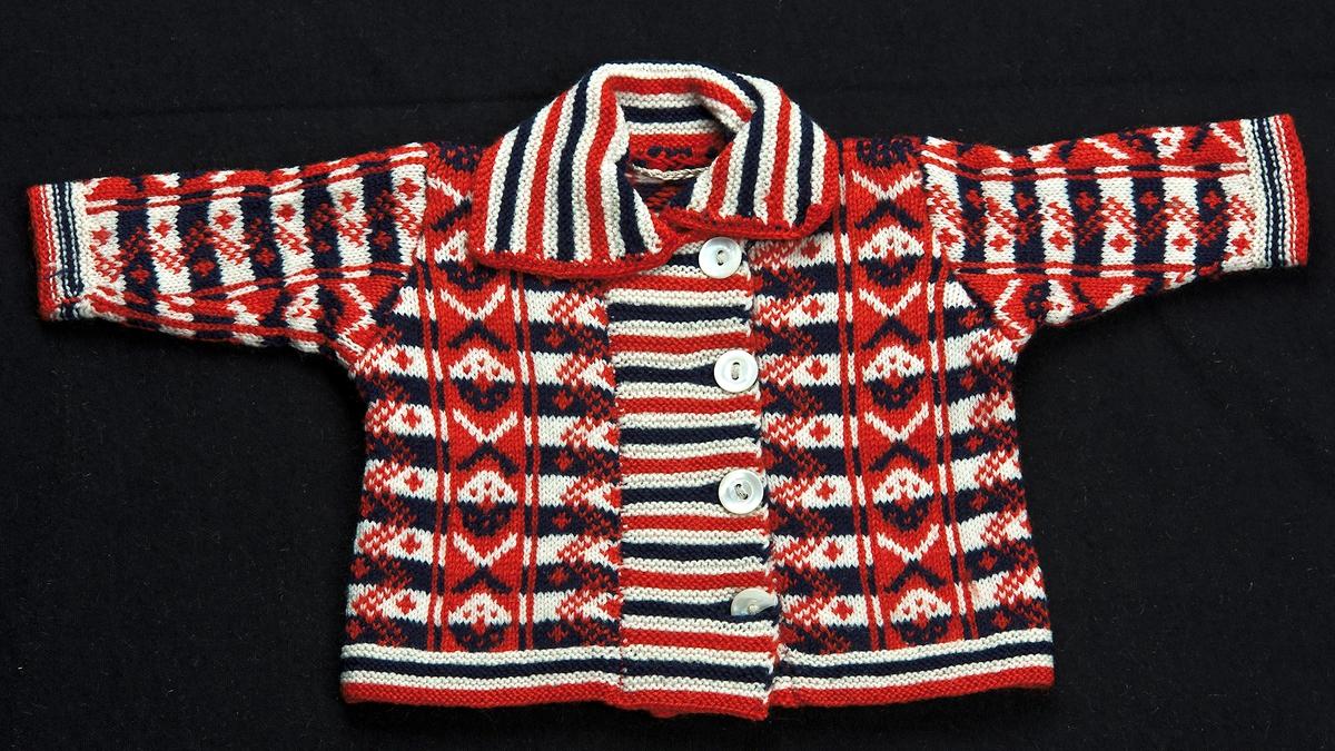 Dockjacka stickad i Bingestickning med tretrådigt ullgarn i färgerna rött, blått och vitt.Halskant, ärmkanter och nederkant stickad randig i rätstickning och övriga jackan är mönsterstickad i Krokmönster och knäpps ihop med fyra pärlemorknappar
