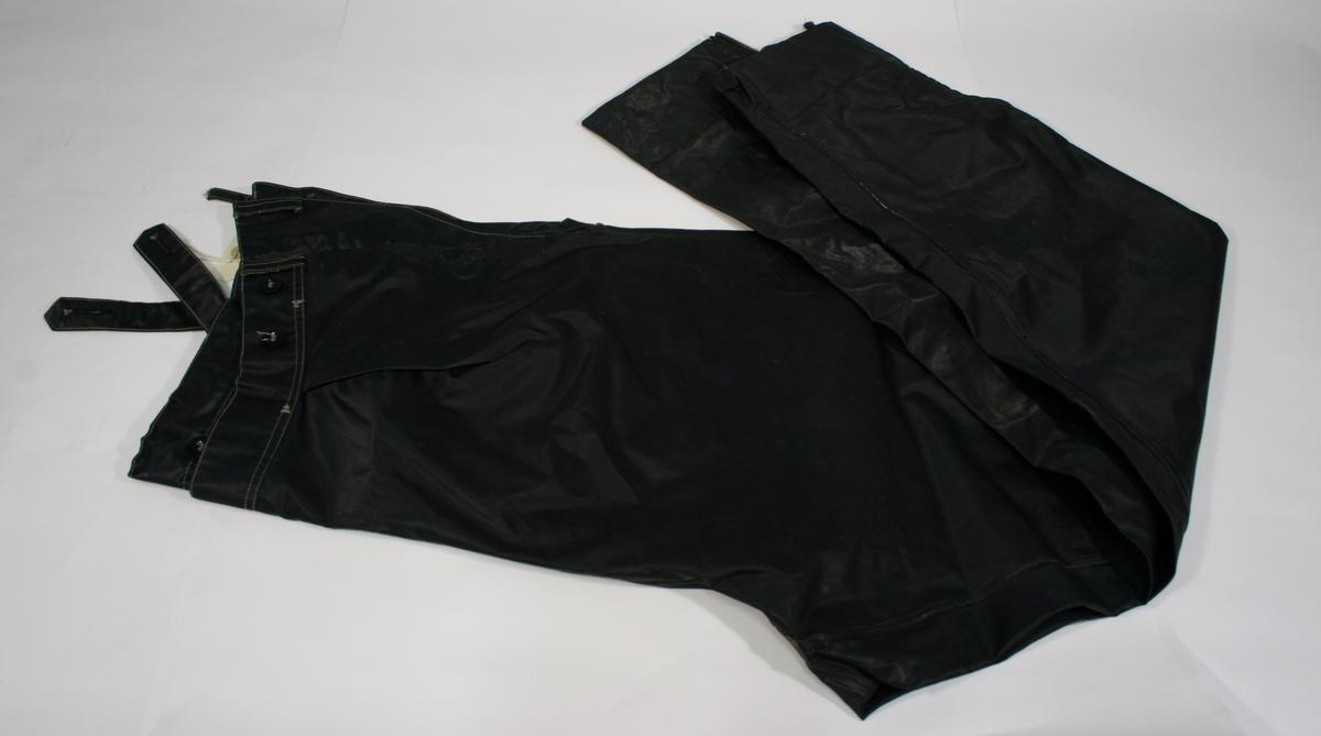 Uniform for motosrsukkelpoliti. Bukse og jakke i sort plaststoff (regntøy). Jakken er lang og er dobbeltspent med løveknapper i gullfarget metall. Hansker i sort skinn med refleksstripe på mansjetten Sort hjelm med politimerking.