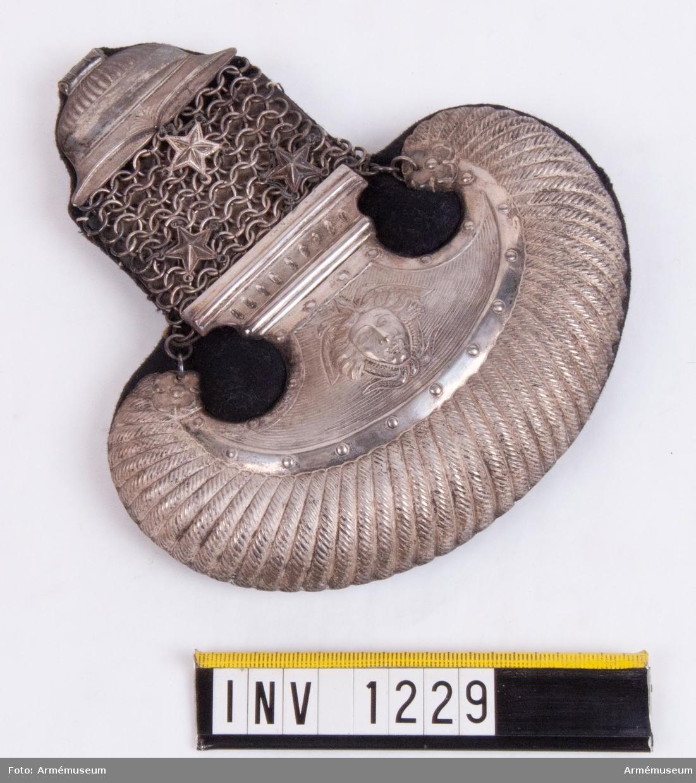 """Av silver (utan synlig stämpel) klädda med svart kläde. Tre stjärnor med kaptens grad. Epåletten består av en ovalformad del och en därifrån utgående rak del. Den ovalformade delen är klädd med ciselerat silver. I mitten ett medusahuvud utformat i metallen. Den raka delen består av knutna eller vävda ringar vilka bildar en matta och där gradbeteckningens tre stjärnor är fästade. Längst upp in mot halsen är metallen formad till en """"mjuk"""" klockform."""