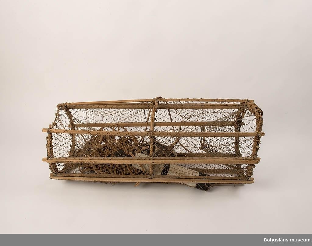 Bågar av trävidjor, sågade käppar, gavelingångar. Lucka på ovansidan. I botten en sten med matnål, en såg med trästickor, en med lås av järntråd. Påknuten lina med mittkork och svart-vitt väle. Mått: L 47 b 7 TJ 6 cm. Tunt nät, små hål.  Ingår i redskapsbestånd ur sjöbod från Hällsö, Havstenssund, Tanum sn. Se UM017521.