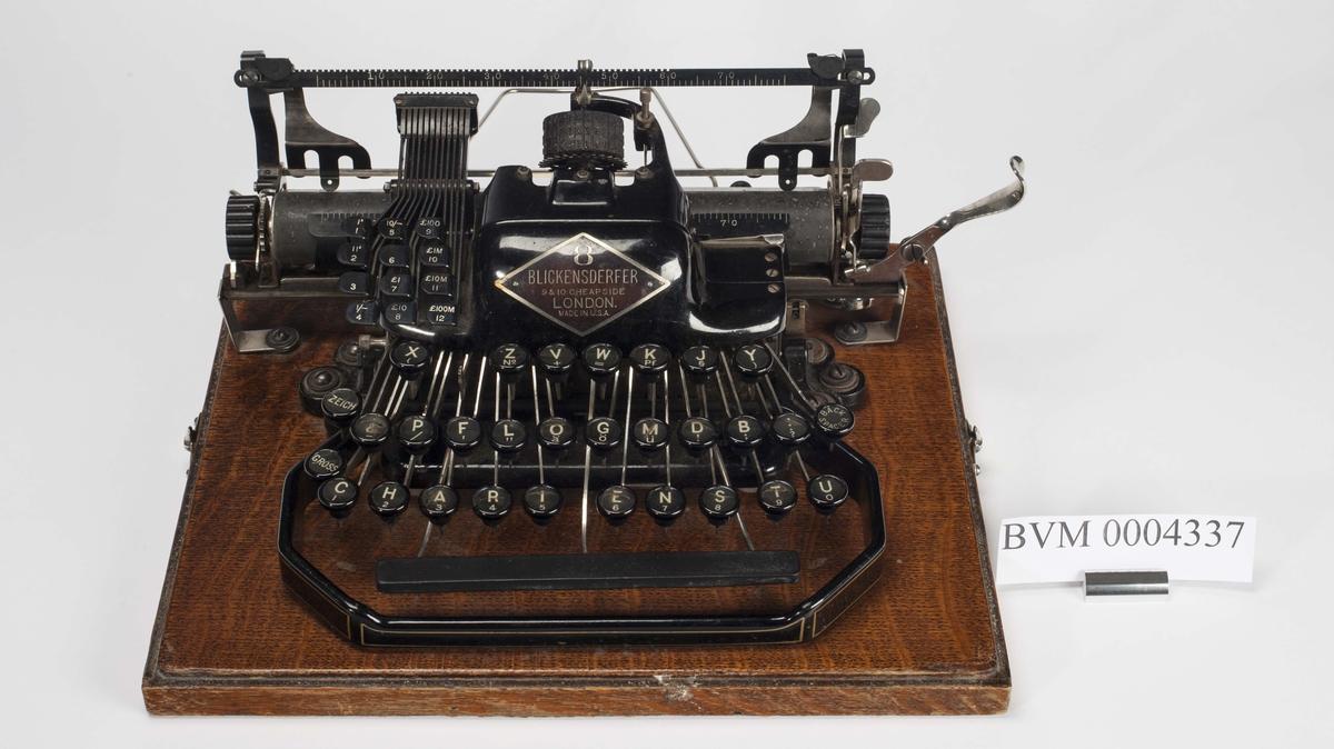 Svartlakkert skrivemaskin av merket Blickensderfer 8. Skivemaskina står montert på ei lakkert treplate som også er bunnen på et reisedeksel. Lokket mangler. Mangler en tast.