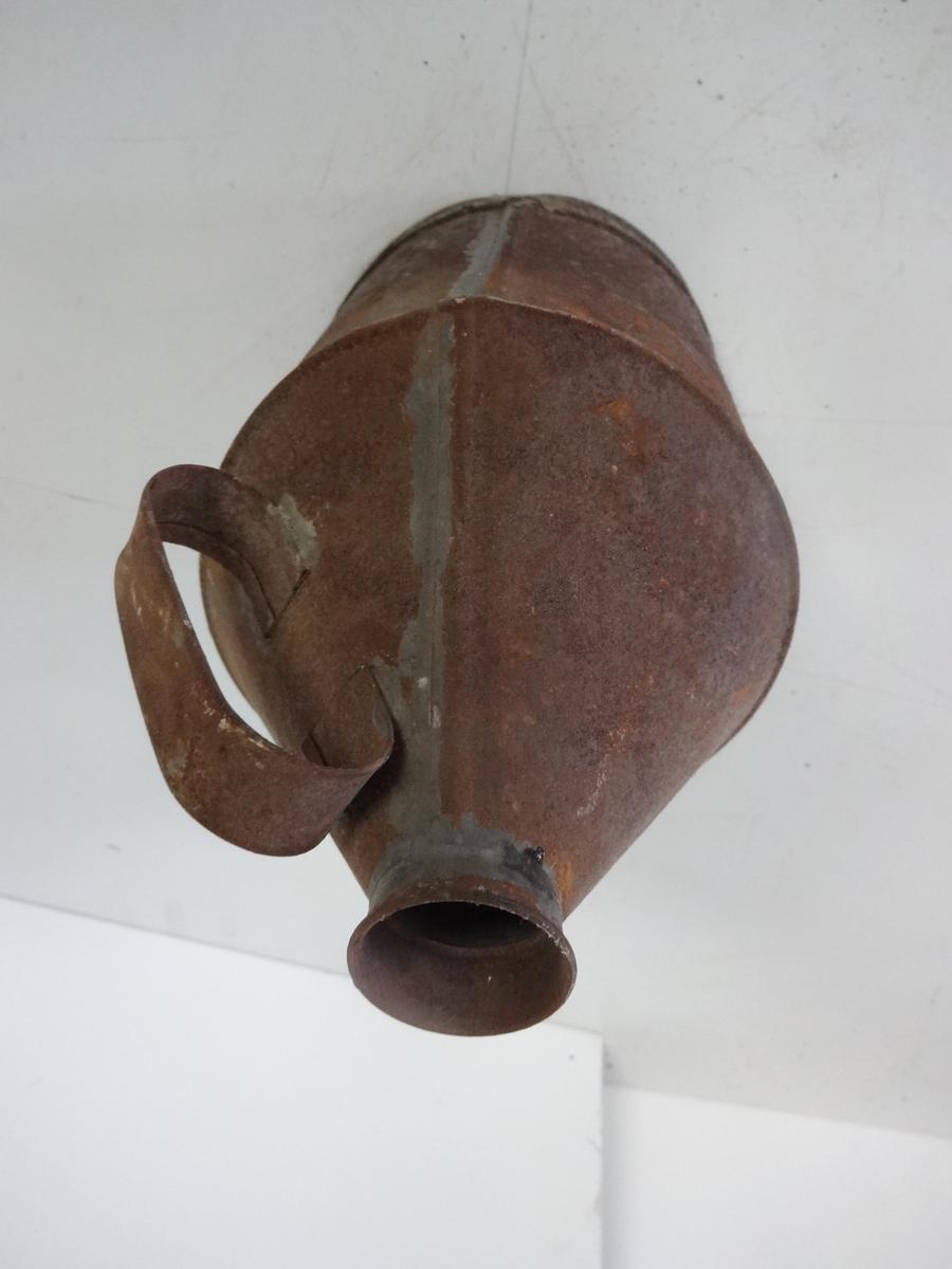 Oljekanne brukt til transport og påfylling av olje/parafin på fyr eller fyrlykter. Kannen har et håndtak.  Kannen er for det meste dekket av rust, men hel. Den har vært blank. Rund konisk form.