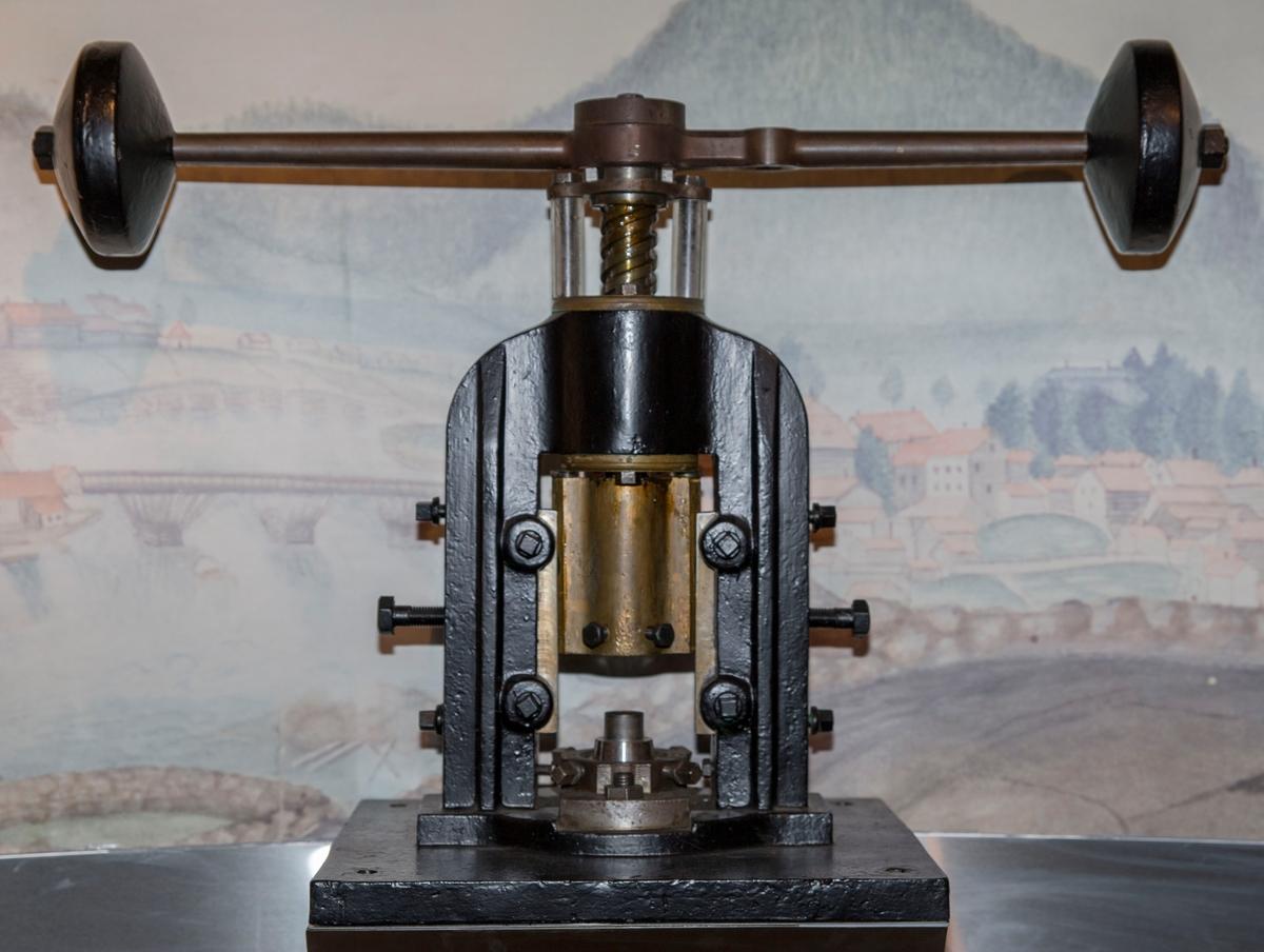 En liten svingpresse. Ett stempel til revers side av en mynt er festet i pressa.