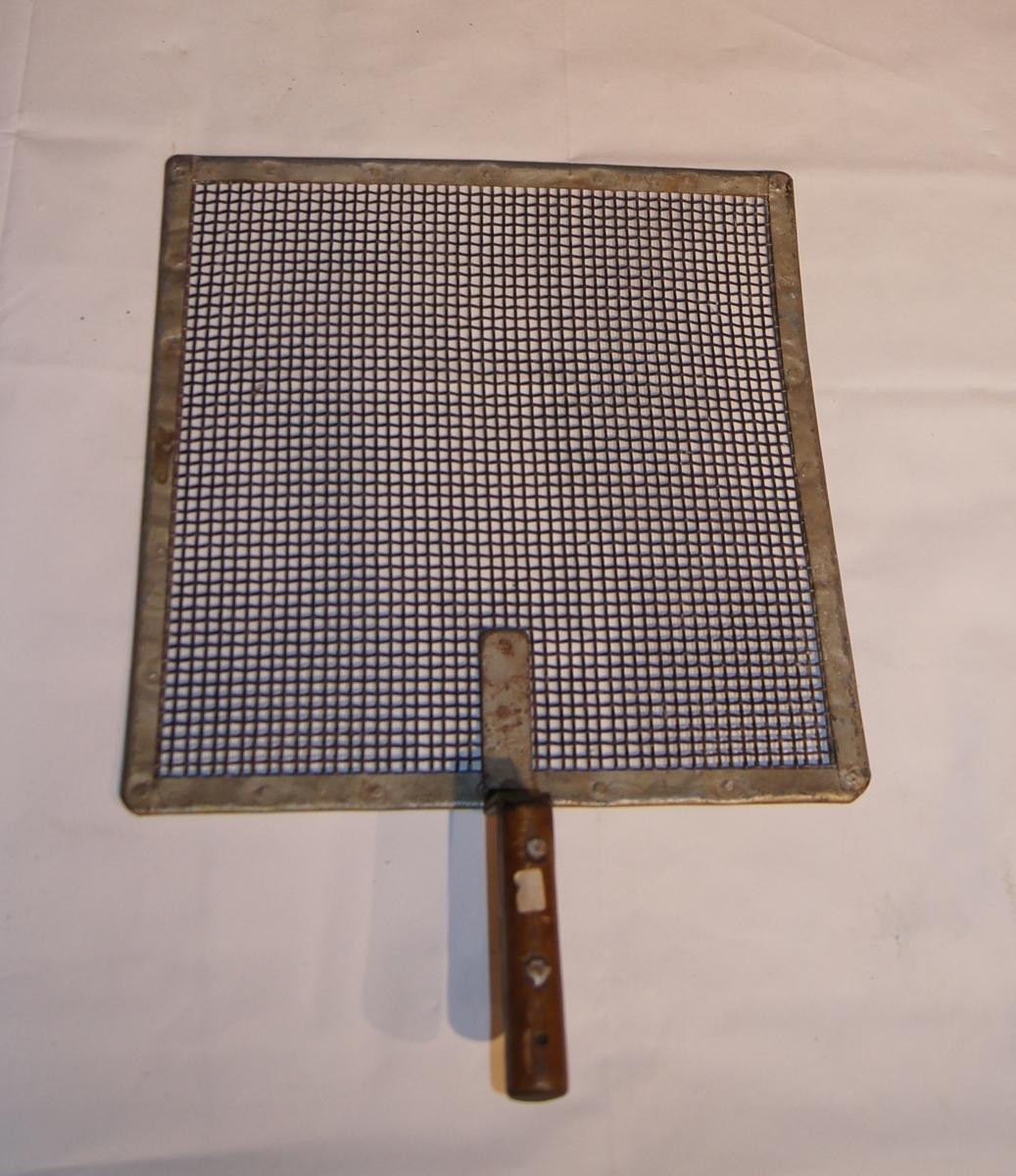 Kvadratisk nettingvisir i metall med håndtak.