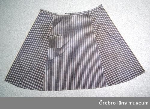 Midjeförkläde av bomullstyg, blå-vit- och rödrandigt. Knäppes runt midjan, en påsydd ficka.Anm: Märta Grapners dödsbo.Neg.nr. 94/83