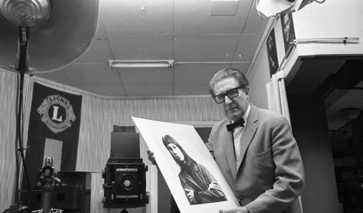 """Götlin, 30 september 1965I förgrunden står står en man klädd i ljus kavaj, vit skjorta med svart fluga till. Han bär glasögon och är fotograf. I sina händer hållar han ett fotografi föreställande en ung flicka som håller en bok i famnen. Bredvid honom till vänster på bilden står en stor kamera och bredvid den ytterligare en kamera som är mindre i storleken. Ytterligare fotoutrustning finns i fotoateljén. På väggen hänger ett tygstycke med texten """"Lions..."""". Ytterligare foton hänger på väggen till höger."""
