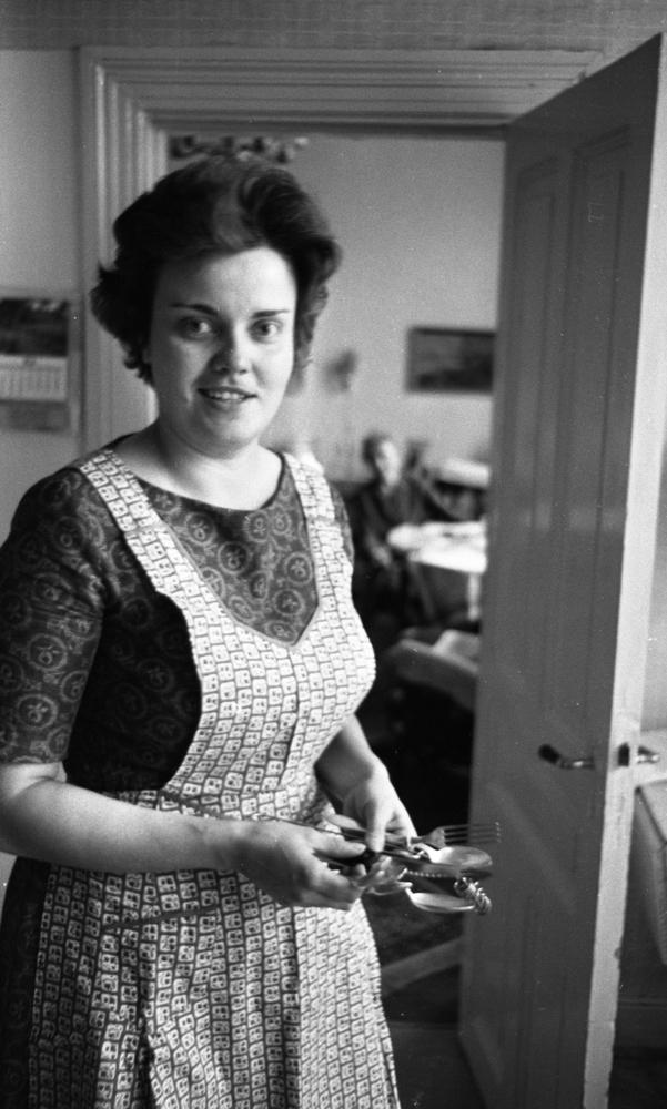 Oddjobb, Hemsamarit 3 september 1965En hemsamarit står med bestick i sina händer. Hon är klädd i en mönstrad klänning med förkläde till. I bakgrunden syns en äldre kvinna som sitter i ett angränsande rum. En dörr står öppen in till rummet.
