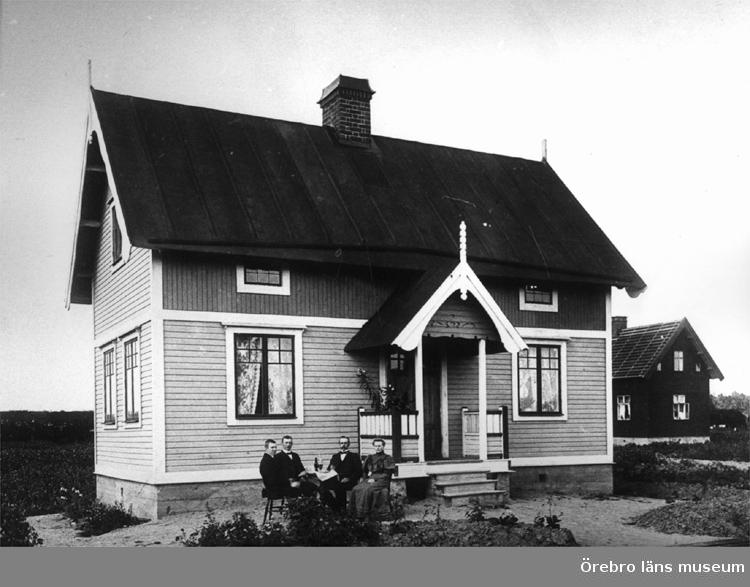 Bostadshus, familjegrupp 4 personer framför huset.