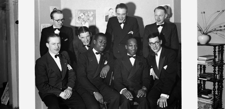 """Gruppbild, 8 personer, i """"Knuttes"""" källarateljé.Sittande från vänster: Knut Borg, """"Happy"""" Mitehner, Roger Boyd och Lars Johansson.Stående från vänster: Rudolf Molin, Olle Johansson, Uno Persson och Filip Andersson."""