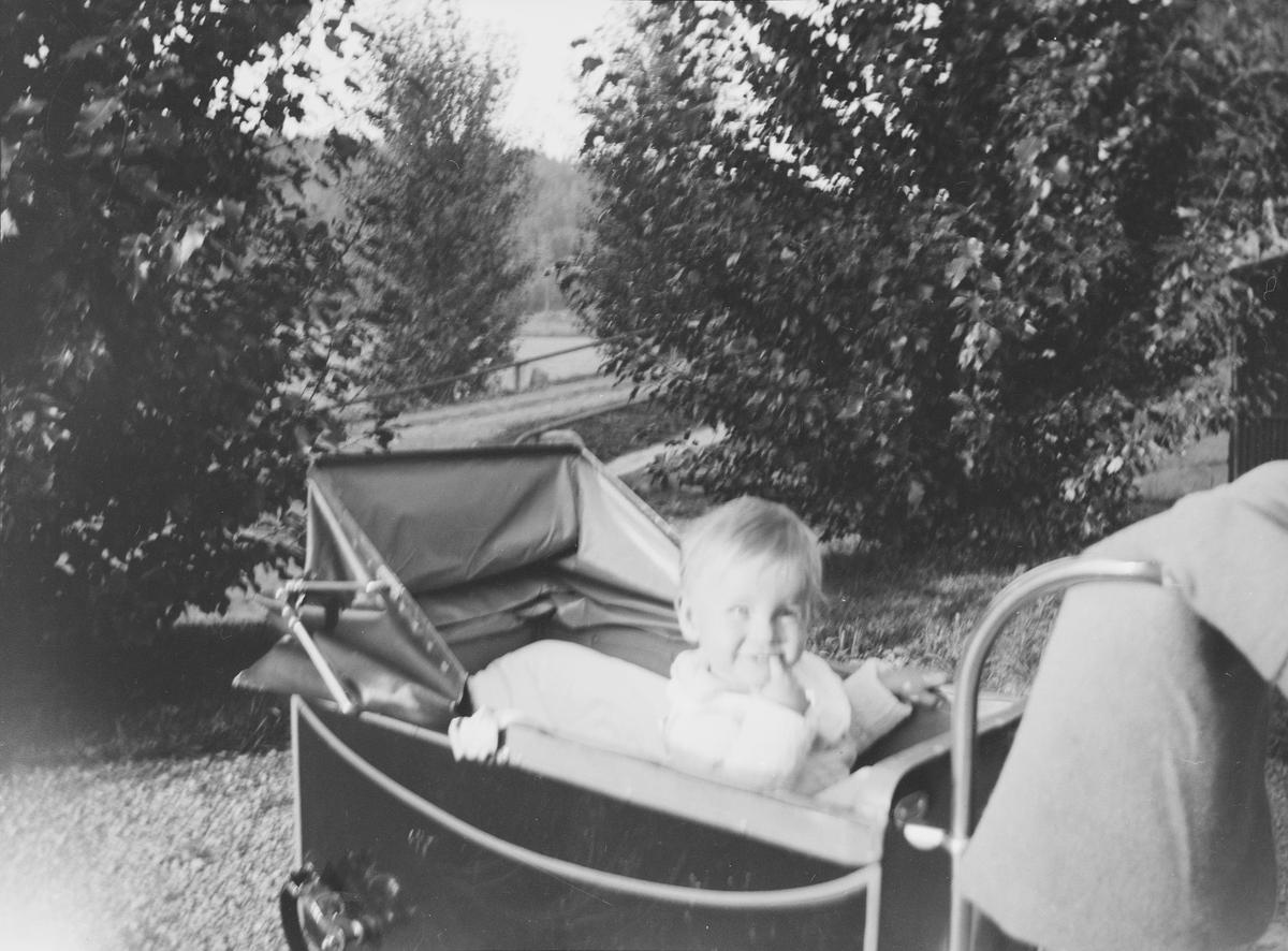 """Et lite barn, lille Pierre, sitter i en barnevogn som står på gårdsplassen til Linderud Gård ved sommerstid. Barnet smiler og """"tygger"""" på en finger."""