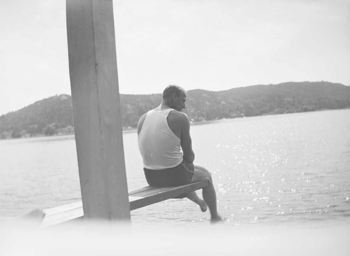 En stolpe deler bildet i to. En mann sitter ytterst på et stupebrett og ser ned mot vannet. Sola skinner.