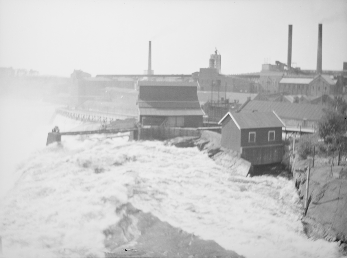 Bildet viser Sarpefossen sett fra Struerveien, fra broen over Glomma. I bakgrunnen sees Borregaards industriområde med fabrikkpiper, store hus av teglstein. I front sees mindre trehus samt ulike broer/byggverk i elva.