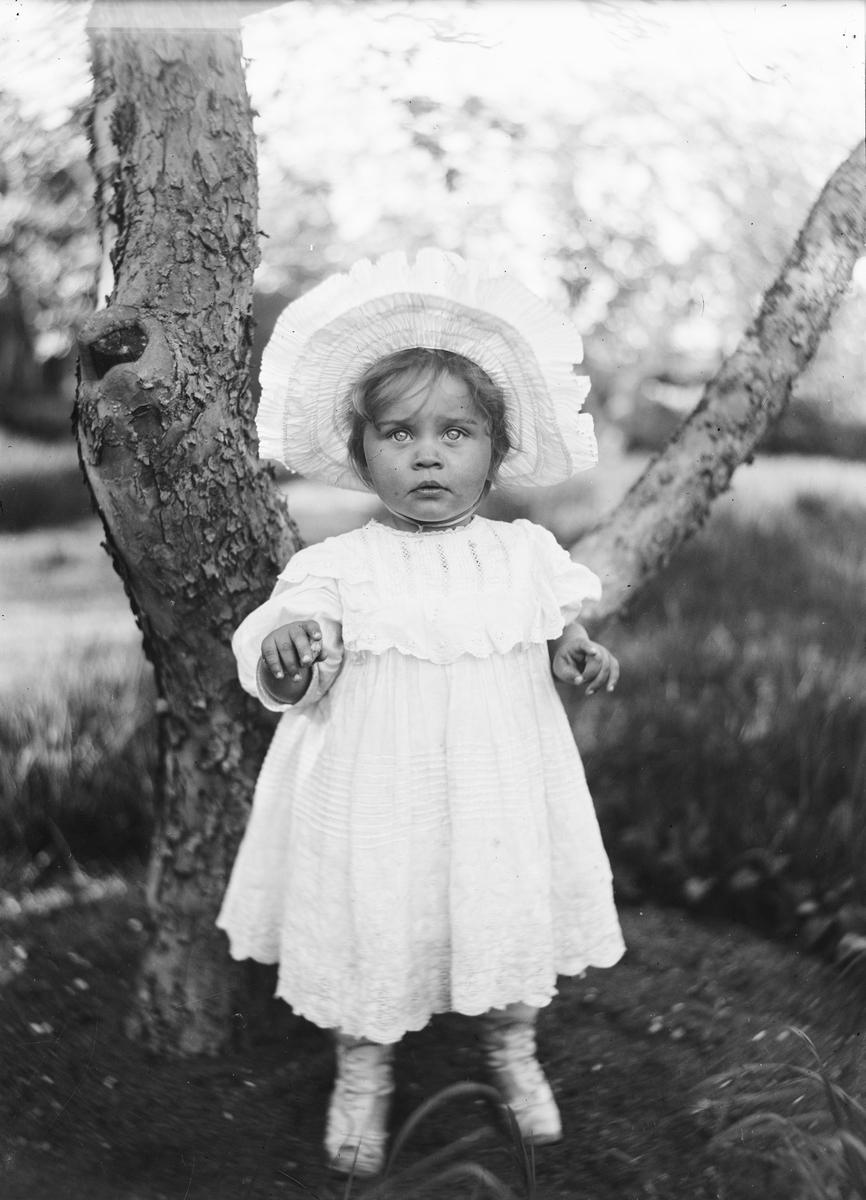 Et barn i kyse og kjole står med hendene mot fotografen. Hun står i sirkeleln uten gress under et tre i en hage.