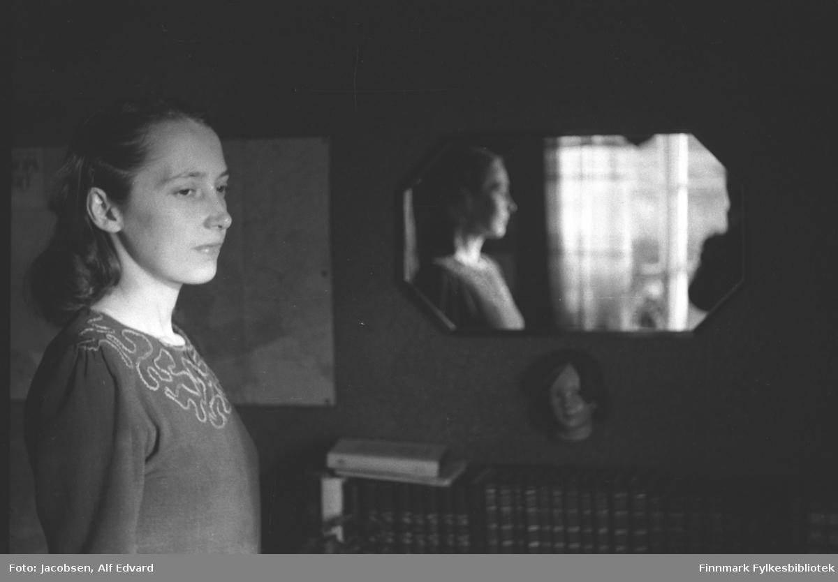 Portrett av Aase Randi Jacobsen. Hun har en ganske mørk genser med et brodert mønster på brystet. Håret er gredd bakover og holdt på plass med hårnåler. På den mørke veggen henger et avlangt speil med avrunnede hjørner og mørk ramme. Speilbildet av henne ses noe diffust. Lyse gardiner foran et vindu ses også der, samt armen på fotografen. Under speilet henger et dukkehodet med mørkt hår på veggen. Nederst på bildet står en liten bokhylle full av bøker, et par bøker ligger oppå. Ved siden av speilet henger en plakat festet med tegnestifter.